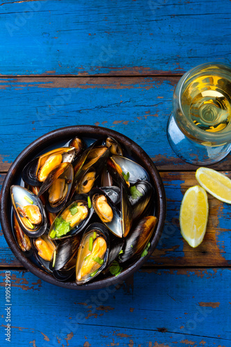 Photo  Mussels in clay bowl, glass of white wine and lemon