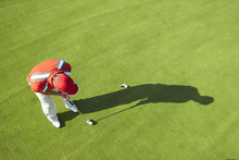 High View Of Golfer And Shadow Putting