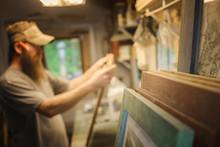 Artist Working In Workshop, Wooden Frames In Foreground