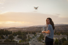 Female Commercial Operator Flying Drone Above Housing Development, Looking Over Shoulder At Camera, Santa Clarita, California, USA