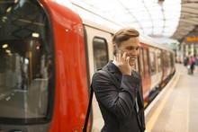 Businessman Using Phone On Platform, Underground Station, London, UK