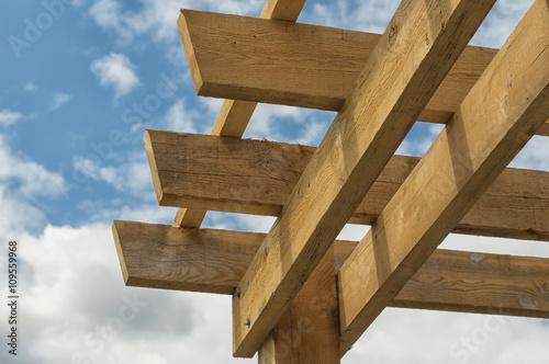 Fotografia  Closeup shot at the corner of a wooden pergola against blue sky