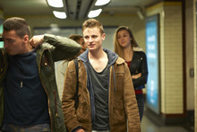 Four Young Adult Friends Walking Through London Underground Station, London, UK