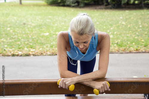 Mature woman taking a break at park bench whilst training in park