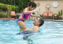 Side View Of Father Lifting Up Girl In Swimming Pool, Face To Face Smiling
