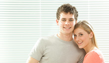 Young Casual Couple In Love With Venetian Blind Window Background