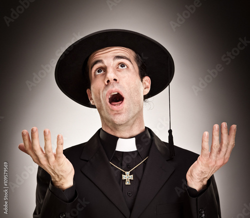 young priest pray portrait on grey background Fototapete
