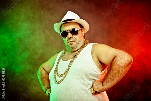 Fotografie, Obraz  italian funny mafia boss rapper with undershirt and sunglasses on smoky backgrou