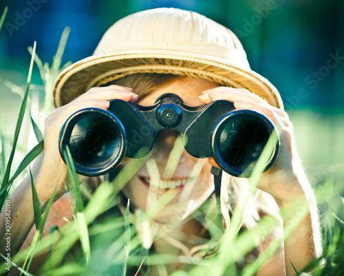 Obraz na płótnie beautiful young explorer girl with hat and binocular at park