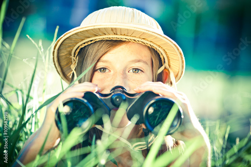 Fotografía beautiful young explorer girl with hat and binocular at park