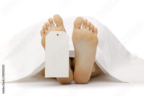 Photo dead body feet with card autopsy isolated on white