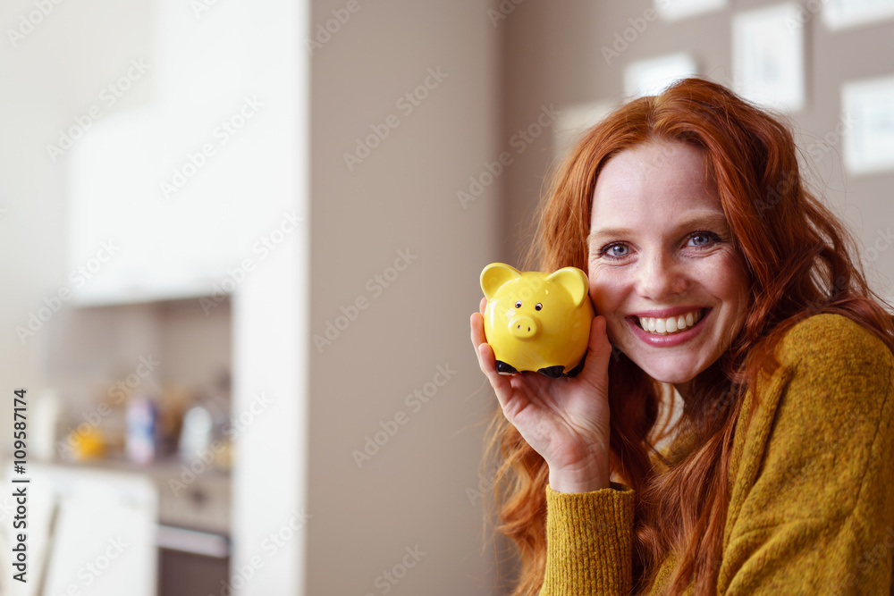 Obraz lachende frau hält sparschwein in der hand fototapeta, plakat