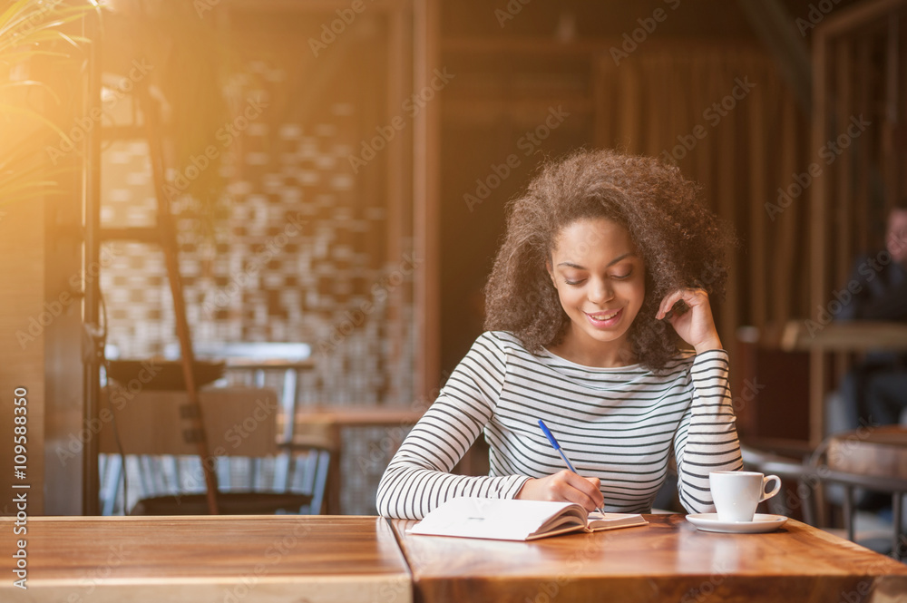 Fototapeta Cheerful young woman is writing in notebook