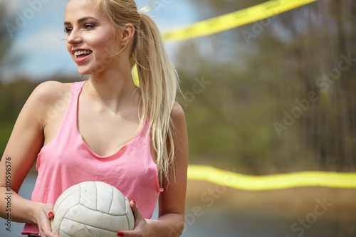 Valokuvatapetti Joyful sexy blond girl playing volleyball outdoors on the lakesi