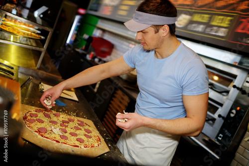 Foto op Canvas Pizzeria Handsome pizzaiolo making pizza at kitchen in pizzeria.