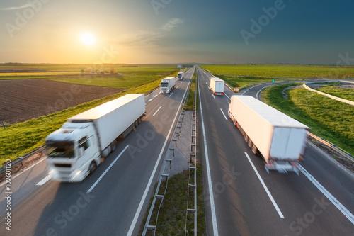 Plakat Duże białe ciężarówki na autostradzie w kierunku zachodzącego słońca