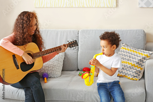 Fotobehang Indiërs Little boy and a young girl playing on guitar in living room.