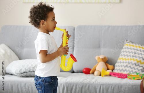 Fotobehang Indiërs Little boy playing on toy saxophone