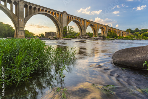 Foto op Aluminium Brug Richmond Railroad Bridge Lit by Sun/ The graceful arches of a railroad bridge spanning the James River in Virginia are illuminated by the setting sun.