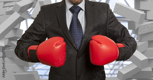 Fotografía Businessman in boxing gloves and brick wall