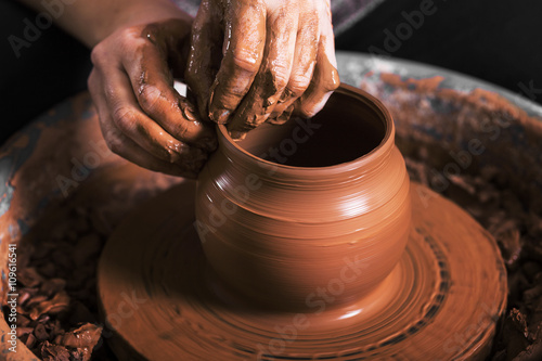 Foto  hands of a potter, creating an earthen jar on the circle