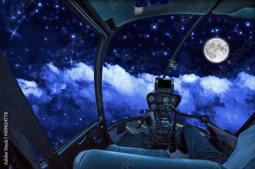 Helicopter cockpit in a cloudy sky at night, with stars and full moon Canvas Print