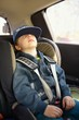 Cute little child sitting in safety car seat and sleeps