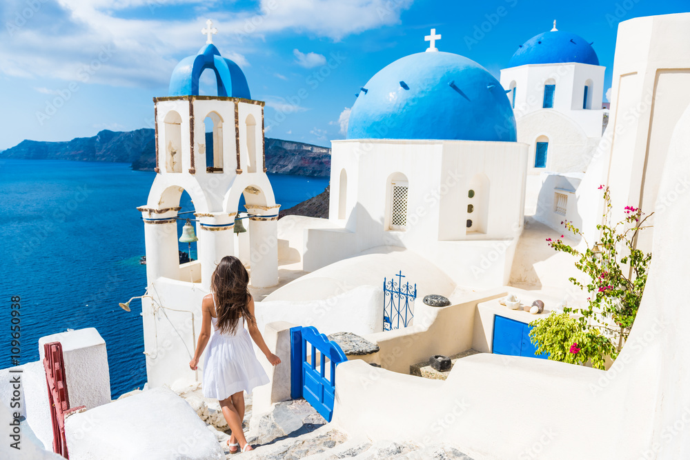 Fototapety, obrazy: Santorini travel tourist woman on vacation in Oia walking on stairs. Person in white dress visiting the famous white village with the mediterranean sea and blue domes. Europe summer destination.