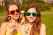 Portrait of happy smiling girls in spectacles holding lollipops