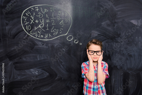 Portrait of young schoolboy in glasses trying to solve difficult Canvas Print