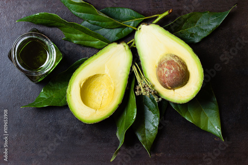Canvas-taulu Avocado with leaves and jar of oil on black background