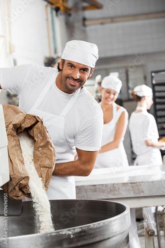 Staande foto Bakkerij Happy Male Baker Pouring Flour In Kneading Machine
