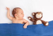 Cute Newborn Baby With A Teddy Bear Under A Blanket