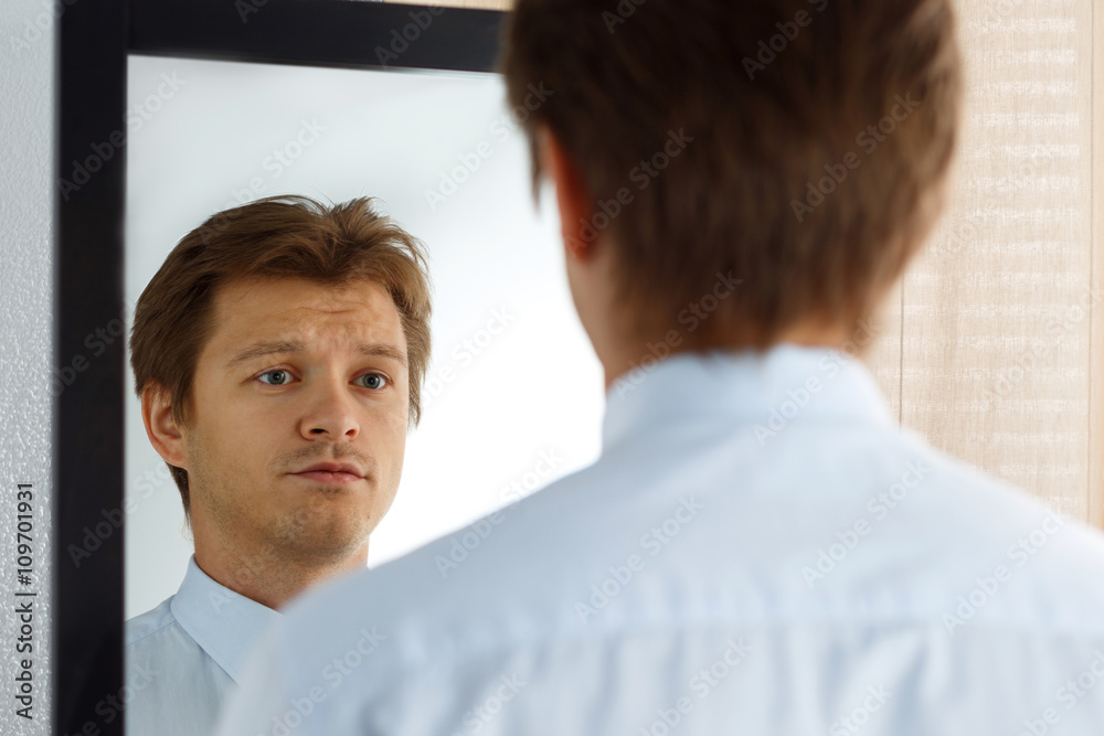 Fototapety, obrazy: Portrait of unsure young businessman with unhappy face