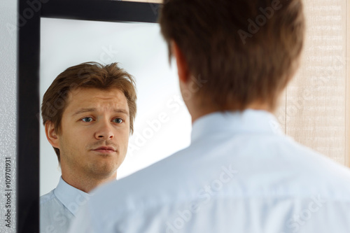 Fototapeta Portrait of unsure young businessman with unhappy face obraz