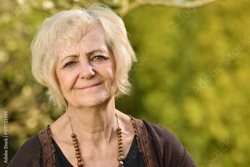 Mature, blonde woman in garden. © itsmejust