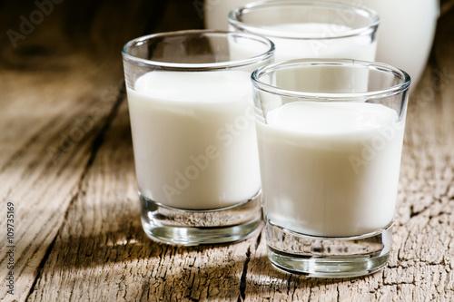 Goat milk in glasses, vintage wooden background, selective focus