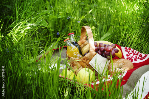 Foto op Plexiglas Picknick Picnic Basket with fruits and drinks on the meadow on a backgrou