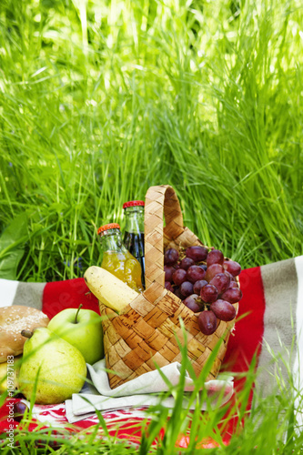 Keuken foto achterwand Picknick Picnic Basket with fruits and drinks on the meadow on a backgrou