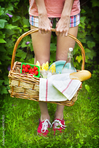 Keuken foto achterwand Picknick Young girl holding a picnic basket with berries, lemonade and br
