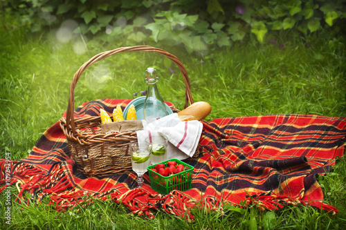 Staande foto Picknick Picnic basket with berries, lemonade, corn and bread.