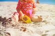 little girl play with toys on beach