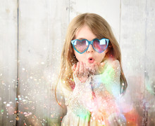 Child Blowing Colorful Party S...