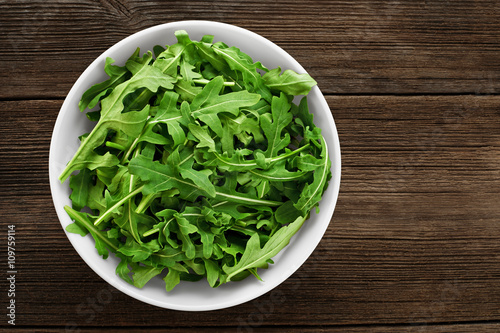 Bowl with fresh green salad arugula on a wooden background Wallpaper Mural