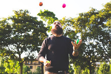 Long Bearded Millennial Bald  Man Juggling With Balls At The Park