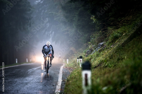 Man cycling on a wet road in rain, Salzburg, Austria Poster