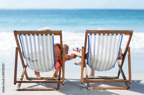 Photo Cute mature couple lying on deckchairs
