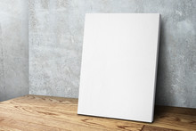 Blank White Canvas Frame Leaning At Concrete Wall And Wood Floor