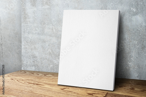 Fotografia, Obraz Blank white canvas frame leaning at concrete wall and wood floor