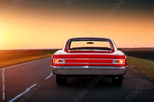 Fotografie, Obraz  Retro red car standing on asphalt road at sunset